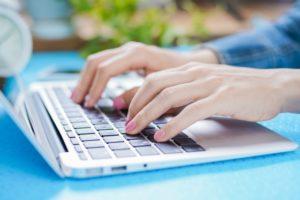ノートパソコンを打つ女性の手 ピンクのマニキュア