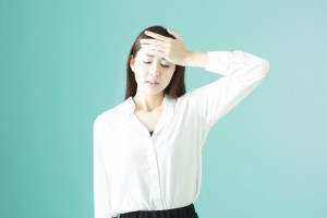 頭痛を感じ額に手をやる女性
