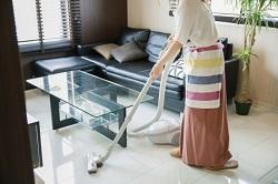 リビングに掃除機をかける主婦