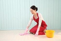 床を拭き掃除する赤いエプロンの女性