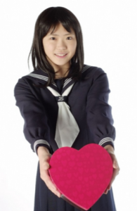 ハート型のプレゼントをする女子生徒