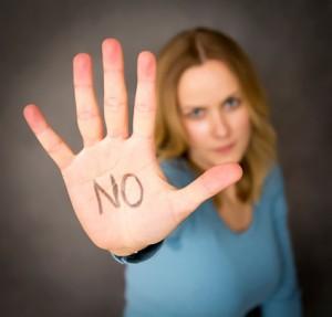 NOと書かれた手の平を見せる外国人女性