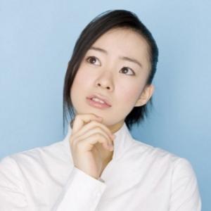 顎に手をやり考える女性