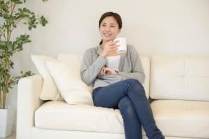 ソファでお茶を飲みながらくつろぐ女性