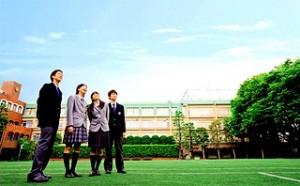 学校の校庭に立つ4人の男女の生徒
