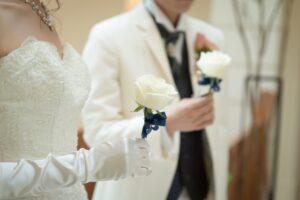 一輪の白いバラを持った新郎新婦