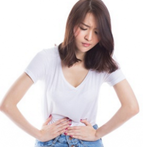 腹痛でお腹を抑える女性