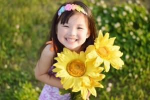 ひまわりを持った笑顔の女の子