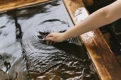 温泉の湯加減を見る女性