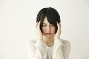 頭痛 こめかみを押さえる女性