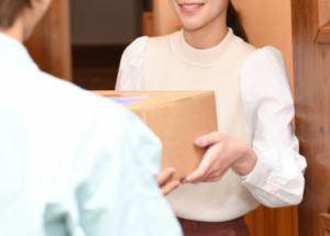 玄関で郵便を受け取る女性