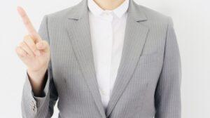 人差し指をたてるスーツの女性