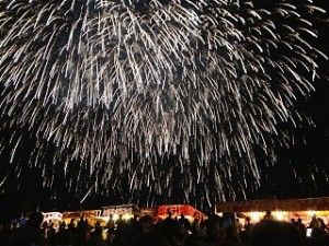 巨大な打ち上げ花火と屋台の列
