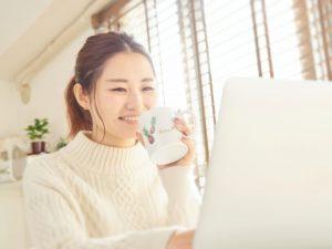 パソコンを見ながらコーヒーを飲む女性