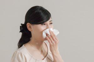 鼻水をティッシュでおさえる女性