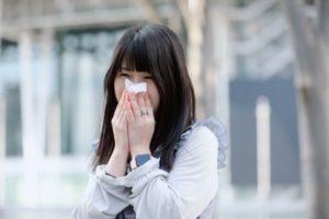 街中で鼻をかむ若い女性