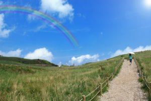 晴天と虹 丘を歩く女性