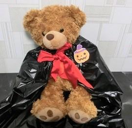 黒のゴミ袋で作ったマントをつけたクマのぬいぐるみ