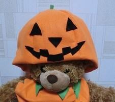 手作りのかぼちゃ衣装をつけたクマのぬいぐるみ