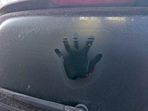 霜が降りた車のリアガラスについた手形