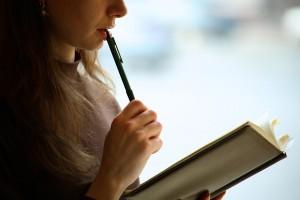 ペンを口に当てて本を見る女性