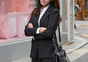 黒のスーツを着て腕組みする女性