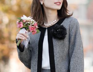 グレーのスーツを着て花束を持った女性