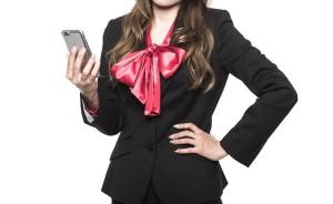 大きいピンクのリボン付きのシャツを着たスーツ姿の女性