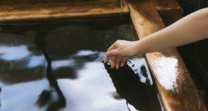 温泉で湯加減を見る女性の手