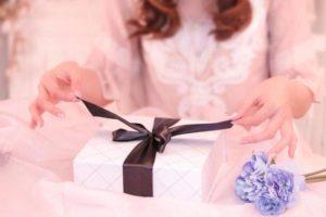 プレゼントの紐を解く女性