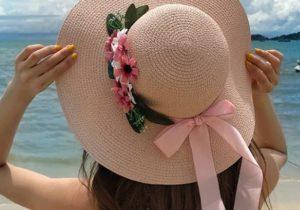 ピンクリボンと花で飾った麦わら帽子 女性 海
