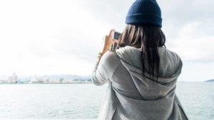 女性 ニット帽 スマホ 海