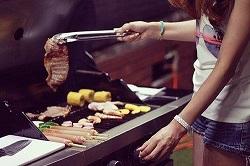 バーベキューでお肉を焼く女性