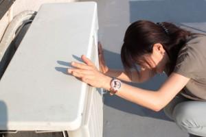 エアコンの室外機を動かす女性