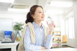 会社でペットボトルの水を飲むOL