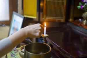 仏壇のろうそくに火を付ける