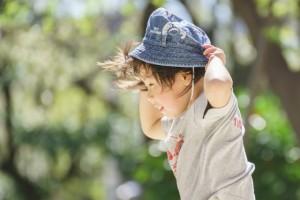 風で飛ばされそうな帽子を抑える男の子