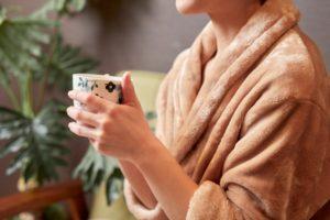 ソファーに座りコーヒーを飲みながらリラックスするガウン姿の女性