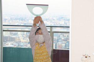 スクイージーで窓拭きする女の子