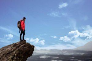 突き出た岩の先で絶景を眺める男性 登山