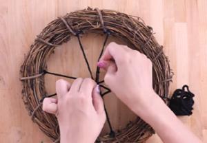 リースに結びつけた毛糸4本の中央にさらに毛糸を結ぶ