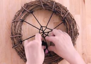 リースに毛糸を螺旋状に絡ませていく