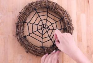 リースに毛糸をクモの巣状に絡ませていく