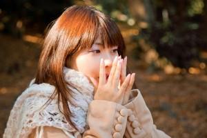 手に息を吐く女性 冬