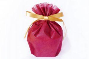 ゴールドのリボンがついたピンクのプレゼント袋
