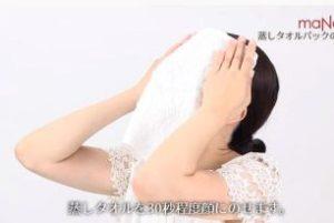 蒸しタオルを顔に乗せる女性