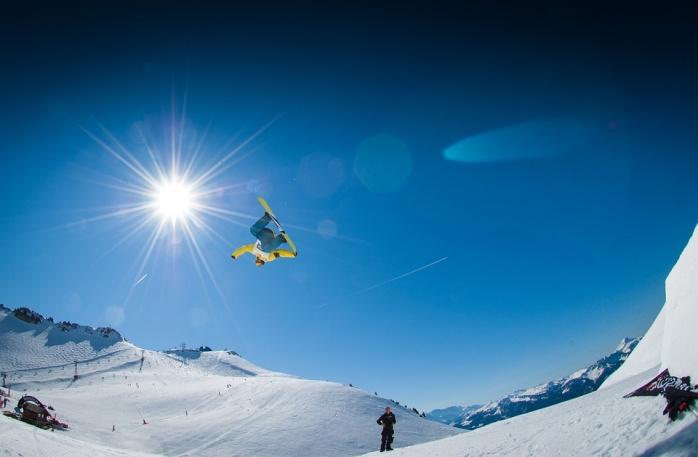 太陽輝くゲレンデで空中回転するスノーボーダー