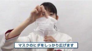 マスクのひだを広げる女性