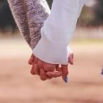 手を結んでいるカップル