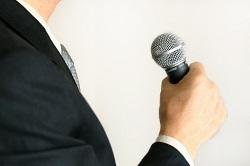 マイクを持ってスピーチをするスーツの男性